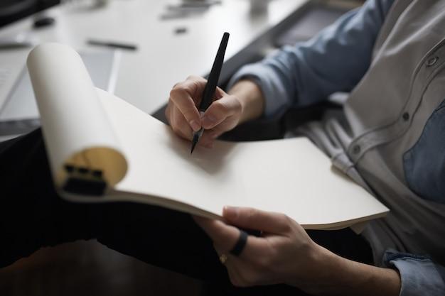 Mani del progettista che disegnano progetto di progettazione.