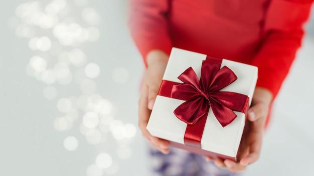 Mani del ragazzino con regalo di natale. irriconoscibile.