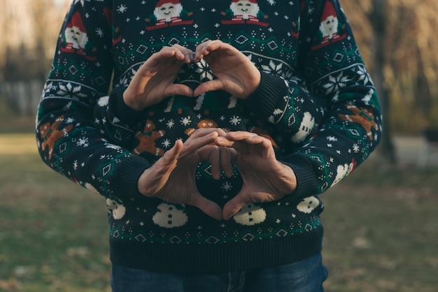 Mani del ragazzo e della ragazza con i vestiti di natale