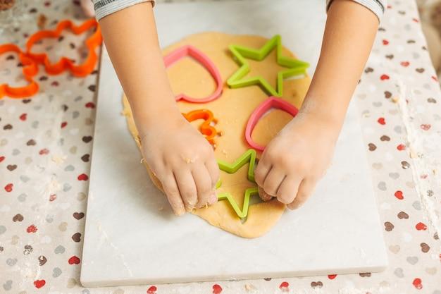 Mani del ragazzo prescolare che produce i biscotti facendo uso delle muffe del biscotto
