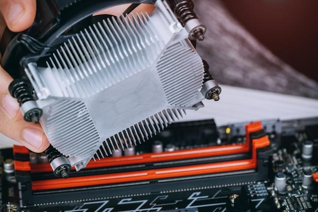 Mani del tecnico che installano la ventola del dispositivo di raffreddamento della cpu su una scheda madre del pc del computer