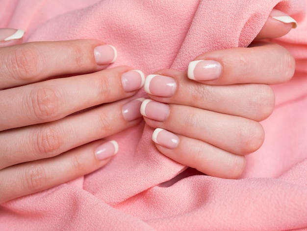 Mani delicate della donna che tengono tessuto rosa