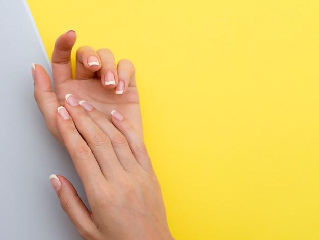 Mani delicate della donna con lo spazio giallo della copia