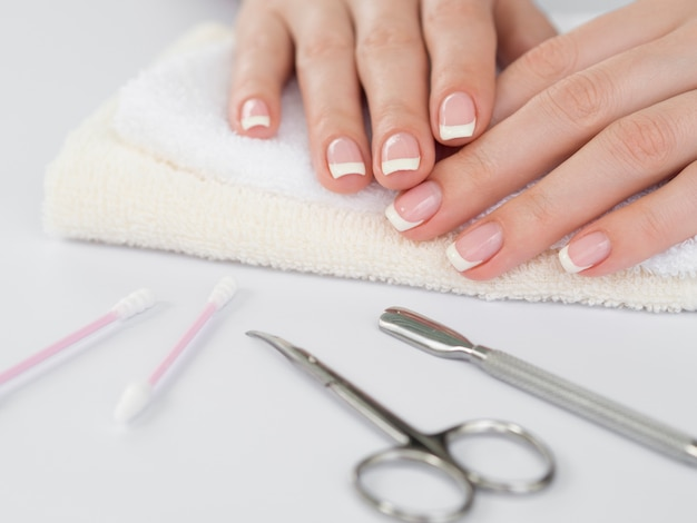 Mani delicate della donna e strumenti di manicure