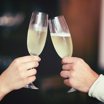 Mani dell'uomo e della donna che tostano con Champagne