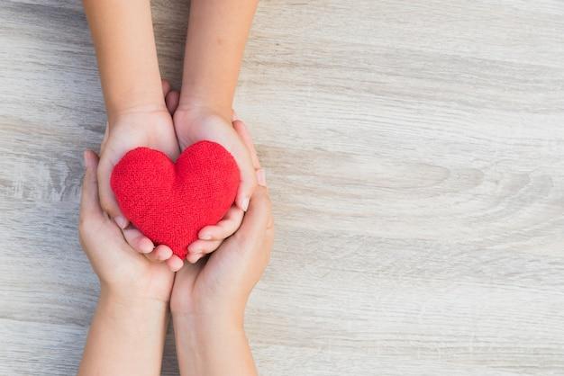Mani dell'adulto e del bambino che tengono cuore rosso fatto a mano su fondo di legno.