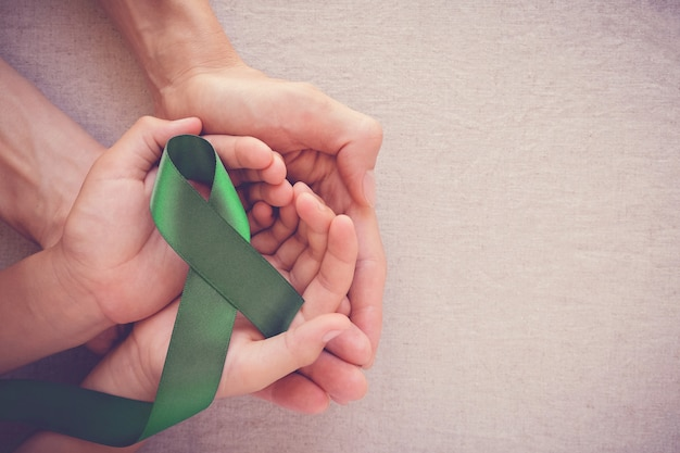 Mani dell'adulto e del bambino che tengono nastro verde, consapevolezza del cancro