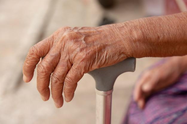 Mani dell'anziana asia con un bastone da passeggio della canna