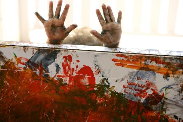 Mani dell'artista dei bambini che dipingono i multi colori