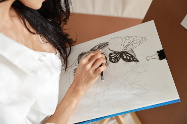 Mani dell'artista donna in camicia bianca disegno immagine con la matita (concetto di stile di vita della donna)