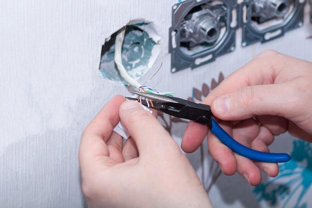 Mani dell'elettricista che installano presa a muro, fine su.