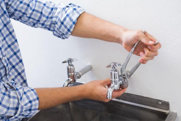 Mani dell'idraulico che riparano il colpetto di acqua con le pinze
