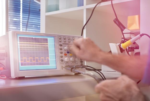 Mani dell'ingegnere maschio senior che sintonizzano oscilloscopio digitale nell'officina riparazioni dell'hardware