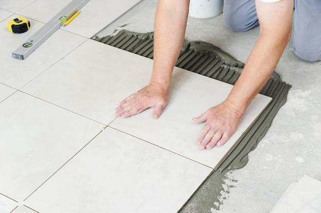 Mani dell'operaio che premono piastrella di ceramica per pavimentare