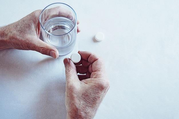 Mani dell'uomo anziano che prendono una pillola con un bicchiere d'acqua
