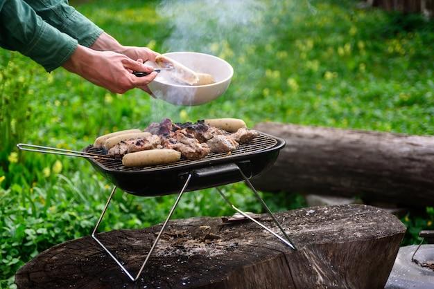 Mani dell'uomo che cucinano la griglia del bbq