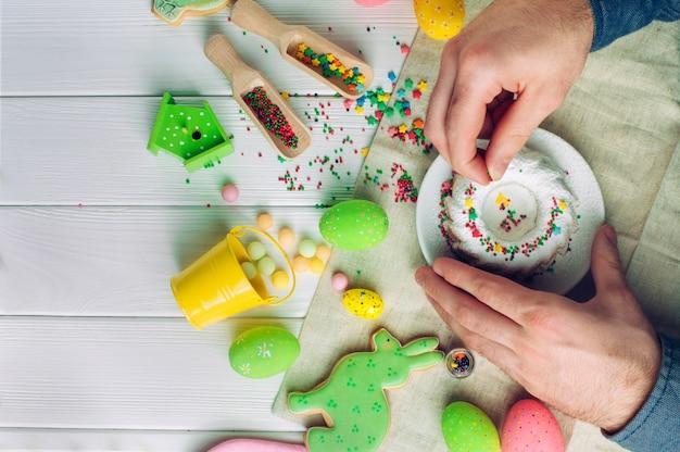 Mani dell'uomo che decorano la torta di pasqua con granelli di zucchero