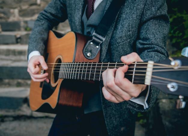 Mani dell'uomo che suonano la chitarra acustica