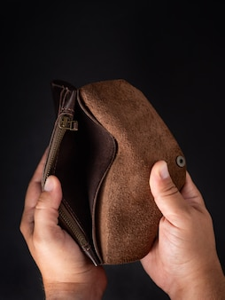 Mani dell'uomo che tengono un portafoglio vuoto