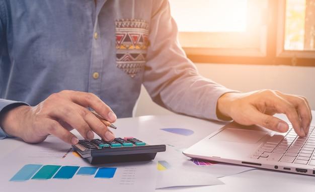 Mani dell'uomo d'affari che lavorano al computer portatile e al calcolatore con i grafici di dati