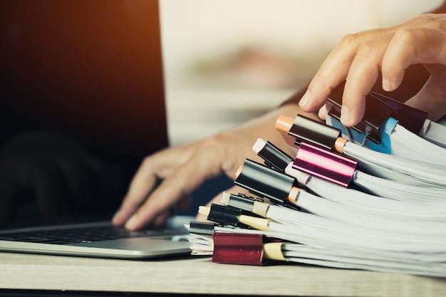 Mani dell'uomo d'affari che lavorano in pile di archivi cartacei alla ricerca di informazioni