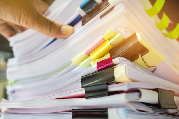Mani dell'uomo d'affari che lavorano in pile di archivi cartacei per la ricerca di informazioni sull'ufficio scrivania