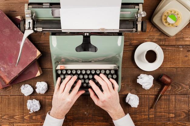 Mani dell'uomo d'affari che scrivono su una vecchia macchina da scrivere