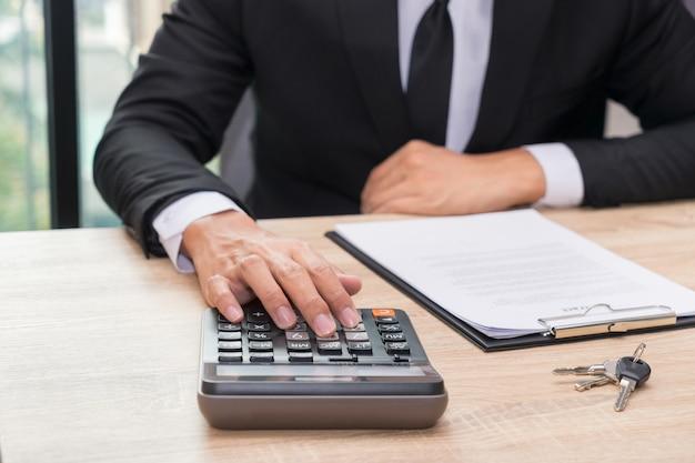 Mani dell'uomo d'affari che spingono calcolatore per il calcolo dell'equilibrio di credito di prestito - concetto finanziario.