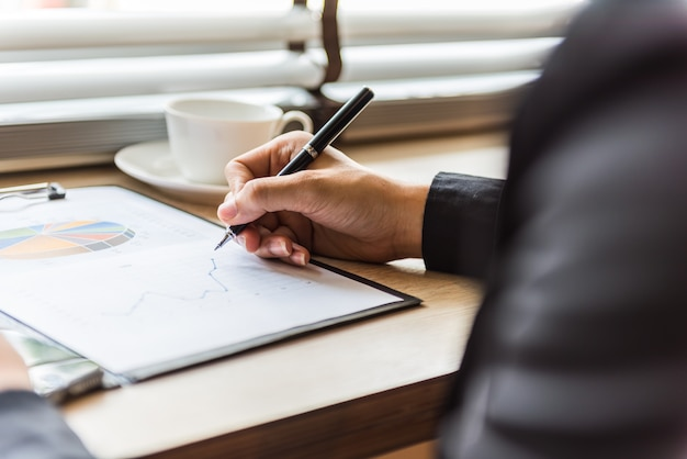 Mani dell'uomo d'affari con la penna che scrive la carta di statistiche grafiche sulla fine della tavola della scrivania su