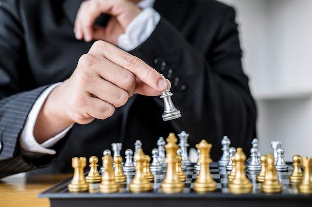 Mani dell'uomo d'affari sicuro che giocano il gioco di scacchi all'analisi di sviluppo nuovo piano di strategia