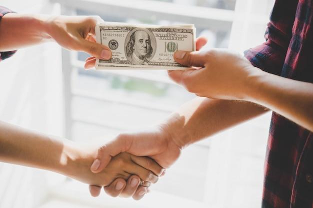 Mani dell'uomo di affari che passano soldi sopra un affare di affari