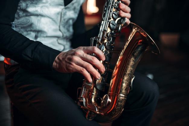 Mani dell'uomo di jazz che tengono il primo piano del sassofono