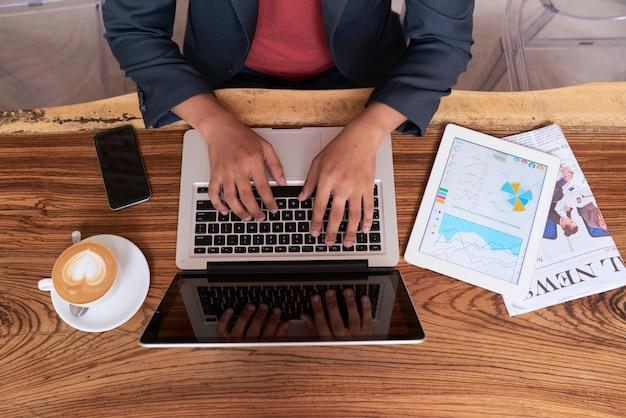 Mani dell'uomo irriconoscibile che si siede alla tavola di legno in caffè e che lavora al computer portatile