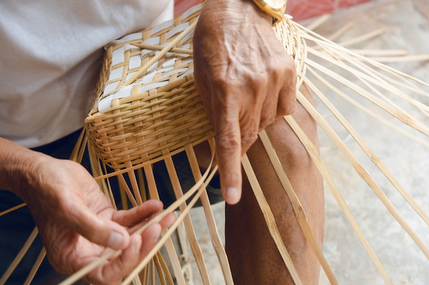 Mani dell'uomo senior che tessono manualmente bambù.
