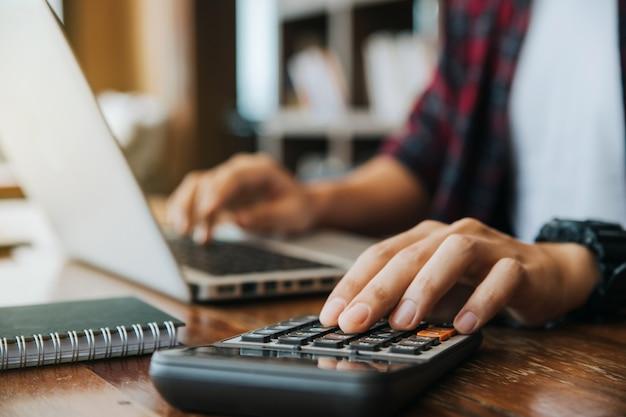 Mani dell'uomo utilizzando una calcolatrice e un computer portatile per il calcolo con la carta di finanza