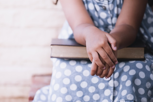 Mani della bambina su un libro. tonalità di colore vintage