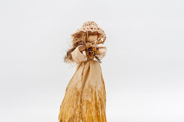 Mani della bambola della buccia di cereale con i fiori su bianco