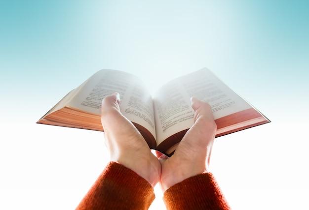 Mani della donna alza una bibbia per pregare