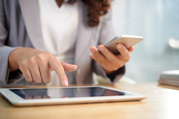 Mani della donna anonima di affari che per mezzo della compressa e dello smartphone digitali sul lavoro