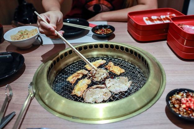 Mani della donna che arrostiscono la carne coreana del barbecue con la bacchette