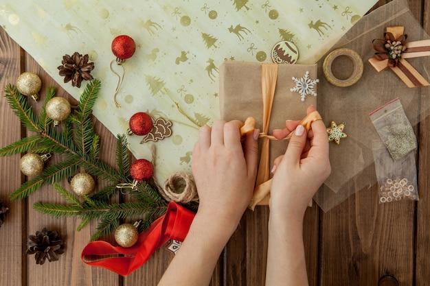 Mani della donna che avvolgono il regalo di natale
