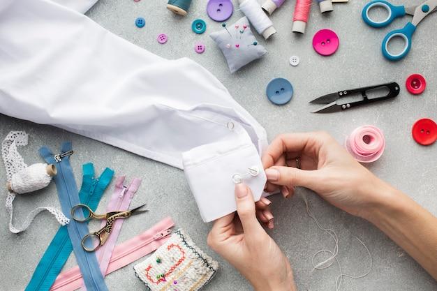 Mani della donna che cuce una vista superiore della camicia bianca
