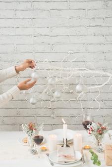 Mani della donna che decorano il ramo di albero con le bagattelle accanto alla tavola di natale sistemata con gusto