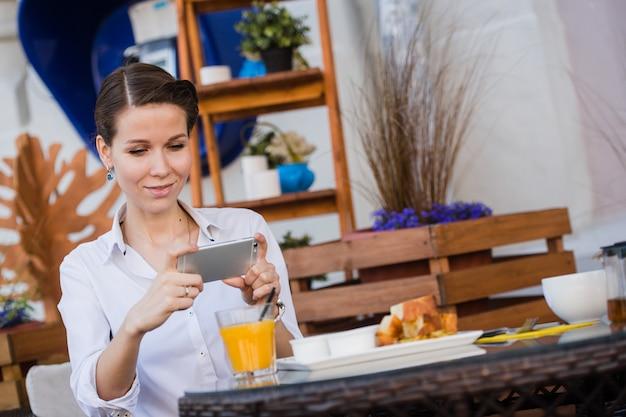 Mani della donna che prendono la foto dell'alimento dal telefono cellulare. fotografia di cibo. deliziosa colazione