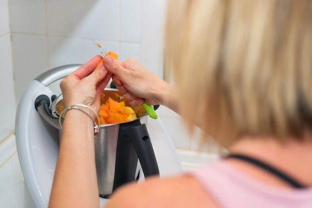Mani della donna che preparano la purea della zucca in macchina del cuoco