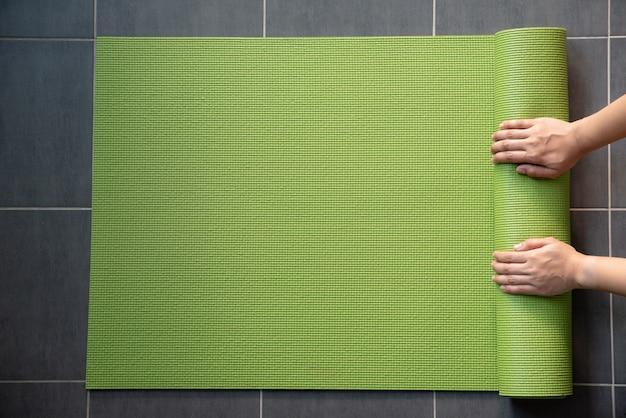 Mani della donna che rotolano il compagno verde di yoga sul pavimento.