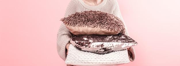 Mani della donna che tengono tre cuscini moderni per il sofà, parete rosa nella tendenza, concetto domestico accogliente pulito di minimalismo