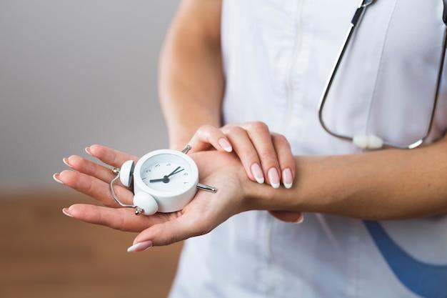 Mani della donna che tengono un piccolo orologio