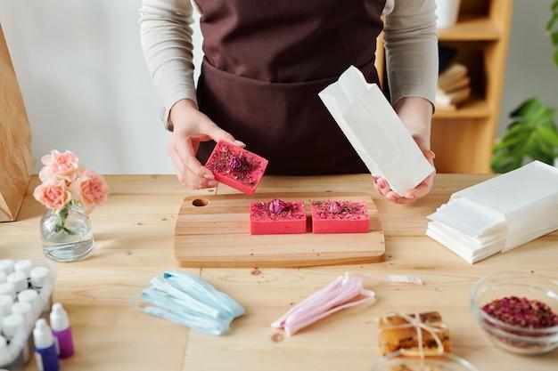 Mani della donna che tiene la barra di sapone fatta a mano e il pacchetto di carta bianca sul tavolo mentre si preparano i regali per le vacanze