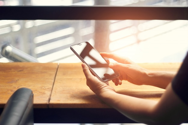 Mani della donna che utilizza smartphone, telefono cellulare, sul tavolo di legno al tramonto sfondo